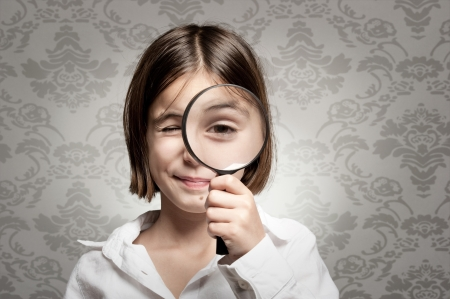 little girl looking at camera through magnifying glass