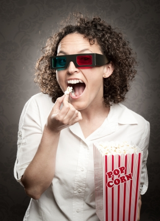 woman wearing 3D glasses and eating popcorn Stock Photo - 17606092