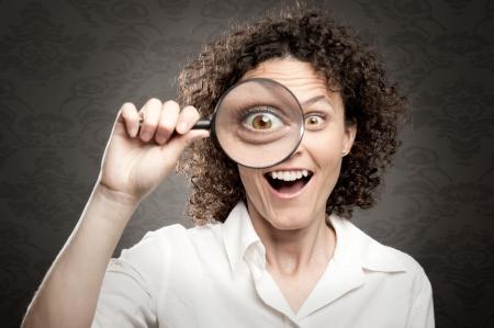 woman looking at camera through magnifying glass photo