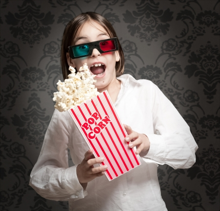little girl wearing 3D glasses and eating popcorn Stock Photo - 17606073