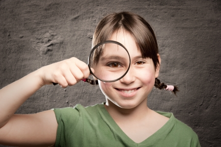 young girl looking at camera through magnifying glass Stock Photo - 17606111
