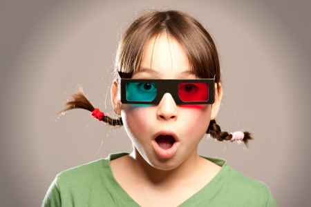 young girl watching a movie wearing 3d glasses photo