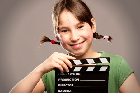 young girl holding a movie clapper board on a grey background