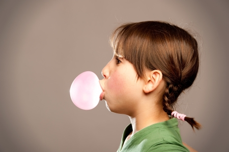 young girl making a bubble from a chewing gum  Stock Photo - 17606101