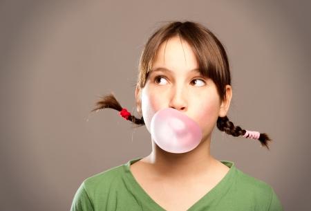 goma de mascar: chica joven que hace una burbuja de una goma de mascar