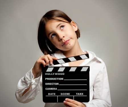 little girl holding a movie clapper board on a grey background Stock Photo - 17606080