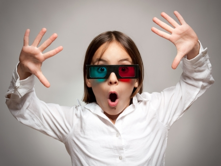 stupor: little girl watching a a movie wearing 3d glasses