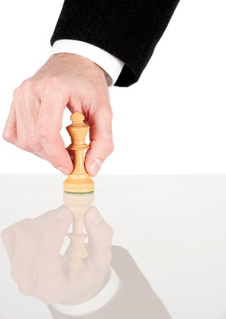 maneuver: businessman hand holding a white king from chess game Stock Photo