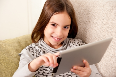 little girl on sofa with touch tablet computer Stock Photo - 17606110
