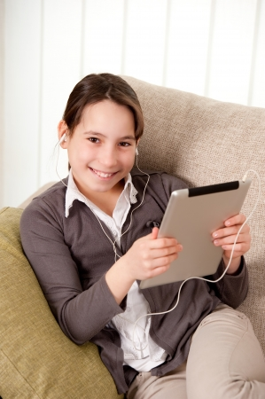 young girl on sofa with touch tablet computer Stock Photo - 17606106