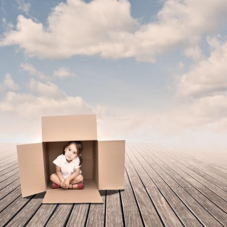 Klein meisje in een doos op een pier Stockfoto