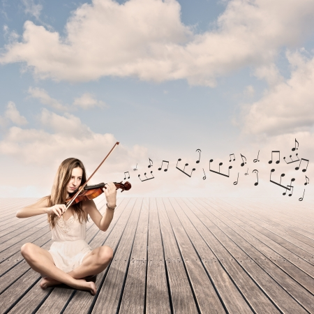 little girl playing violin on a wharf photo