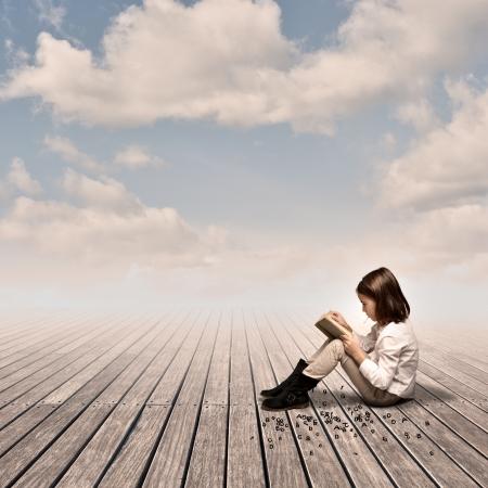 niños leyendo: niña leyendo un libro en un muelle