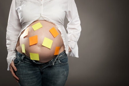 pregnant woman with post it notes on her belly photo