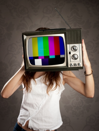 test pattern: young woman with old retro television on her head Stock Photo