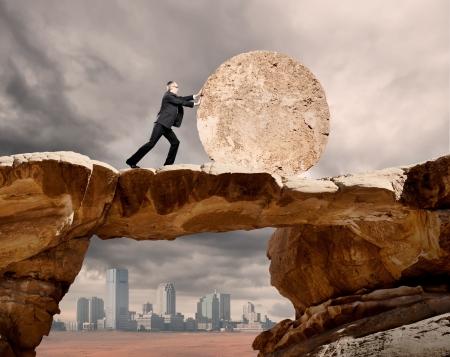 uomo d'affari spingendo una ruota di pietra