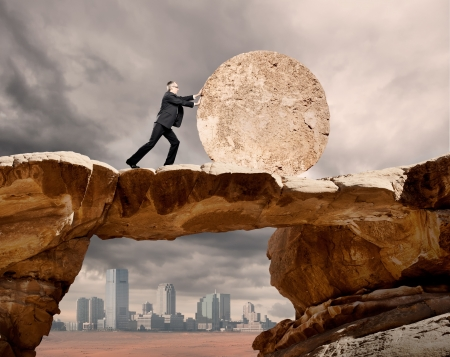 zakenman duwen een stenen wiel