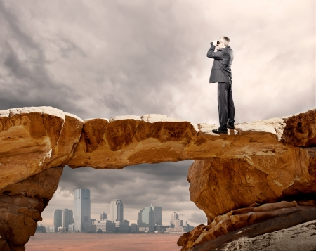 businessman using binoculars on the top of a rock photo