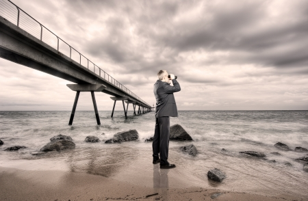 businessman using binoculars on a beach photo