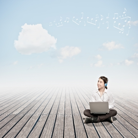 girl holding a laptop and looking to a cloud. Cloud computing concept. photo