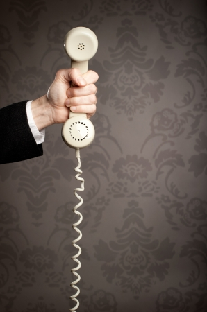 call us: businessman hand holding retro telephone Stock Photo