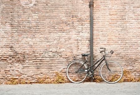 bicicleta retro: antigua bicicleta negro contra una pared de ladrillos Foto de archivo