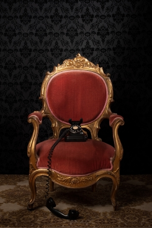 red retro armchair with old telephone photo