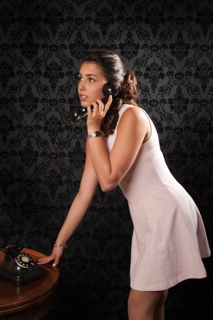 vintage portrait of a beautiful young woman talking by phone photo