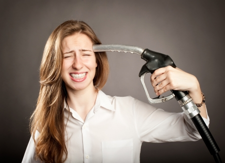 gas pump: young woman shooting herself with a fuel pump nozzle Stock Photo