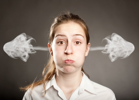 irritated: young businesswoman with smoke on her ears