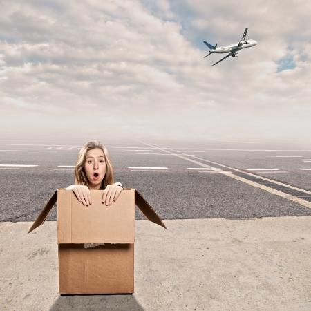 giovane donna all'interno di una scatola in aeroporto