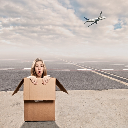 outside box: young woman inside a box at airport Stock Photo