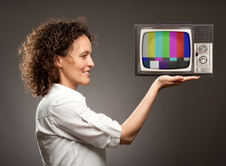 woman holding a television with her hand photo