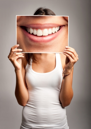 young woman holding a picture of a mouth smiling