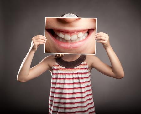 웃는 입의 사진을 들고 어린 소녀 스톡 콘텐츠