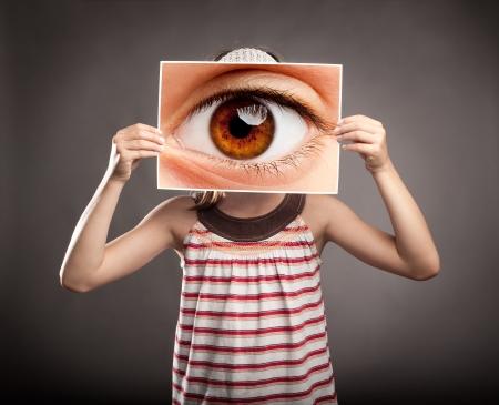 bambina in possesso di una foto di un occhio a guardare