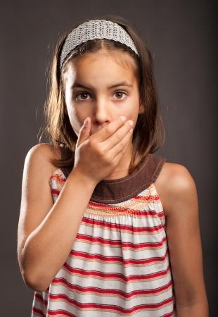 jolie petite fille: petite fille surpris couvrir la bouche avec sa main Banque d'images