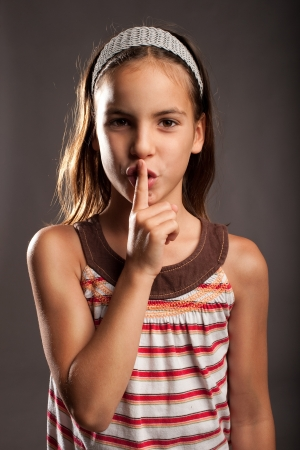 the color of silence: little girl showing silence gesture on a gray background