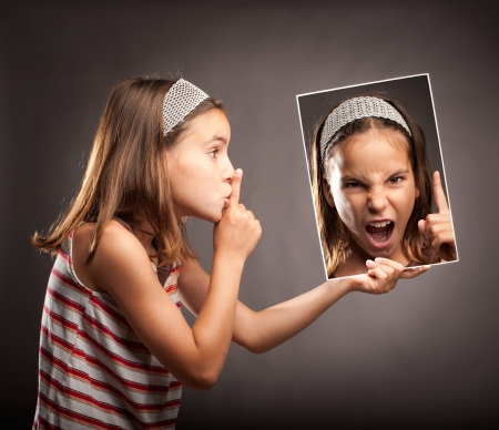 anger kid: little girl showing silence gesture and holding a portrait of herself