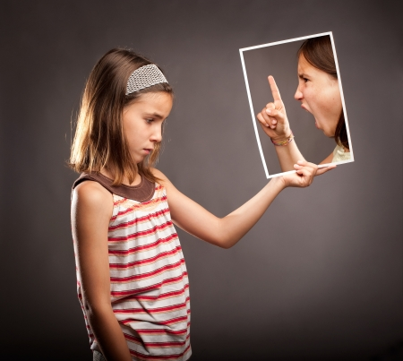 little finger: sad little girl  holding a portrait of an angry girl