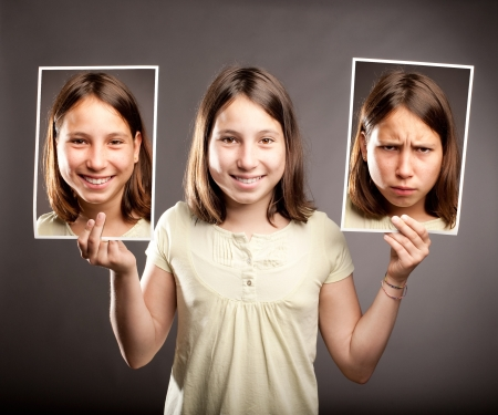 schizophrenia: portrait of young girl holding two photos of herself with happy and sad expressions
