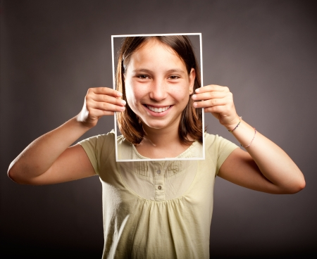 portrait of young girl holding a photography of herself with happy expression Stock Photo - 21626617