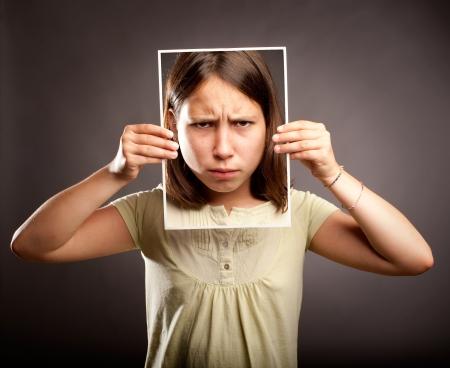 esquizofrenia: Retrato de una chica joven que sostiene una fotografía de ella con expresión triste