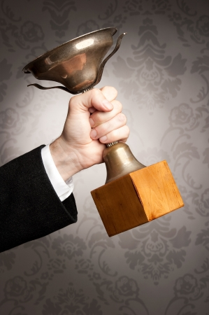 award trophy: businessman hand holding a trophy