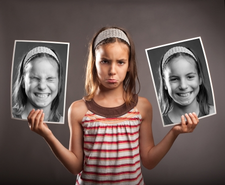 portrait of sad little girl holding two photos of herself with happy expression Stock Photo - 21626644