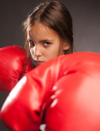little girl wearing red boxing gloves photo