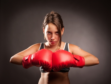 portrait young girl studio: young girl wearing red boxing gloves