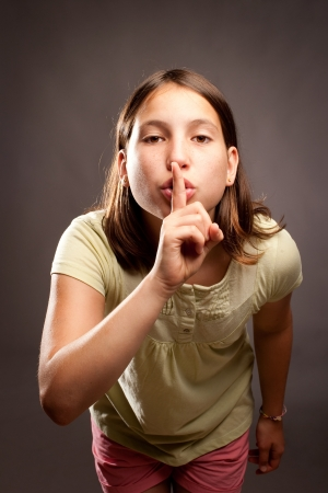the color of silence: young girl showing silence gesture on a gray background