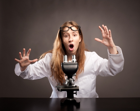 surprised young woman working with a microscope photo