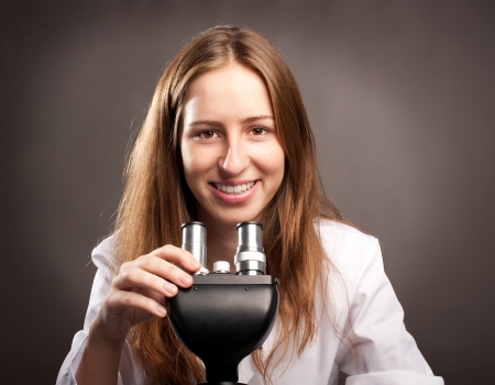young woman working with a microscope photo
